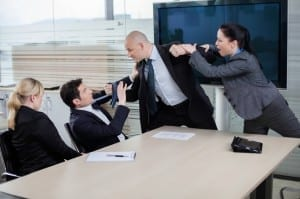 Businessman attacking his colleague at a meeting, grabbing him by the tie and getting ready to punch him in the face. Emotions running high.