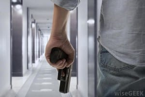 man-walking-down-hall-with-gun